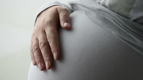 Pregnant woman touching gently her tummy while standing by the window