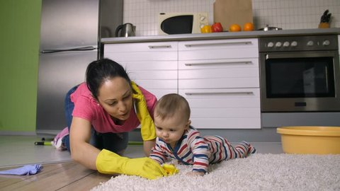 Busy working hispanic mother managing to take care of her baby son, clean and scrub the floor and talk business on mobile phone at the same time. Young woman in rubber gloves housekeeping. Dolly shot