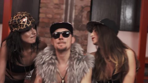Wealthy caucasian rapper man in fur vest with glasses and snapback with sexy girls in underwear sitting on bed covered in money rapping