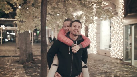 A happy family walks the evening in the city on holidays. The father carries on his back a daughter who tears a leaf from an autumn tree