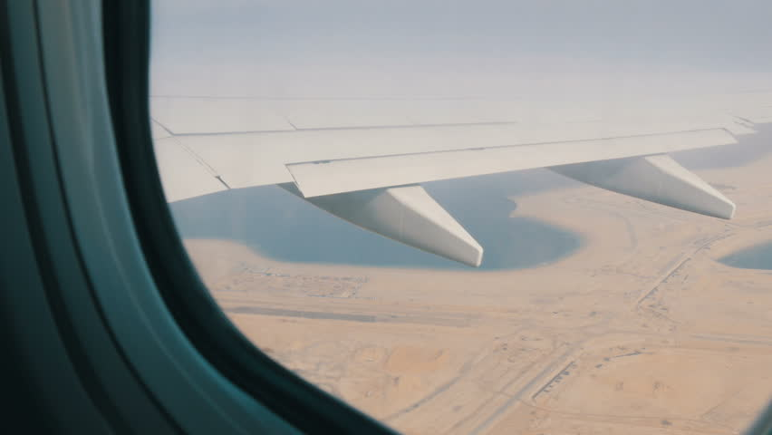 The plane is flying over the desert. Wing an airplane out the window on a background of a desert yellow landscape
