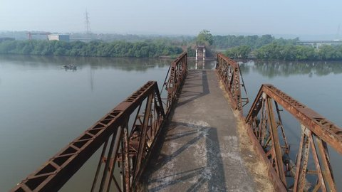 Flying over rusty truss of the demolished bridge over the river Zuari in Goa, India.