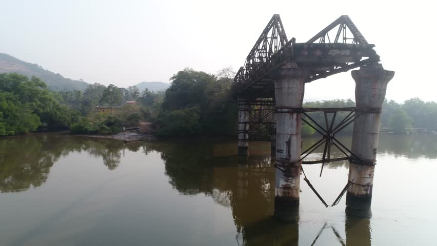 Flying around supports and truss old, rusty, dilapidated bridge over the muddy river on low altitude. Aerial view from a drone. | Shutterstock HD Video #1007526001