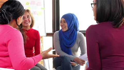 Group of casual multiethnic women in colorful clothes talking in the meeting for social project