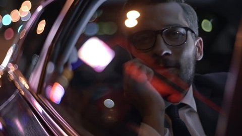 Close up of bearded businessman in glasses and suit talking on mobile phone while riding in backset of car at night