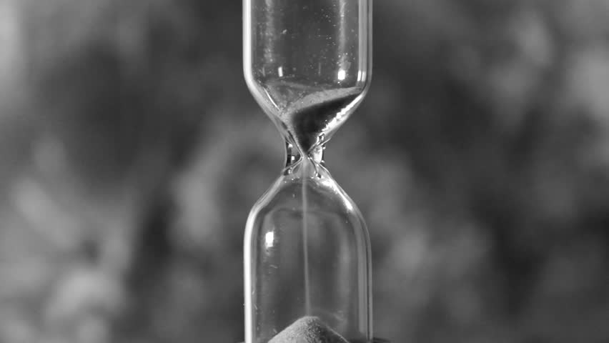 glass hourglass is pouring out the sand expires time
