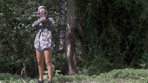 blonde in a camo jacket is shooting from a crossbow. Slow motion