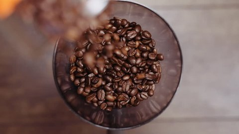 Fresh roasted coffee beans pouring in a grinder from glass jar. Barista man preparing to grind coffee, making freshly ground coffee in electric coffee mill. Top view. Slow motion.