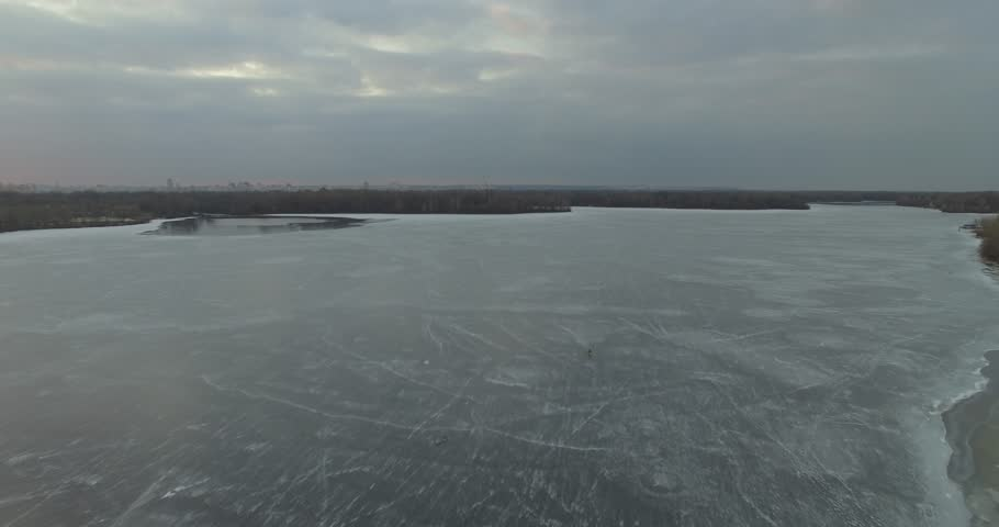 Aerial frozen lake half water half ice, ice floe.Aerial drone bird's eye view of frozen heart shaped lake covered with snow at winter time.Aerial drone shot river and tree reflection.