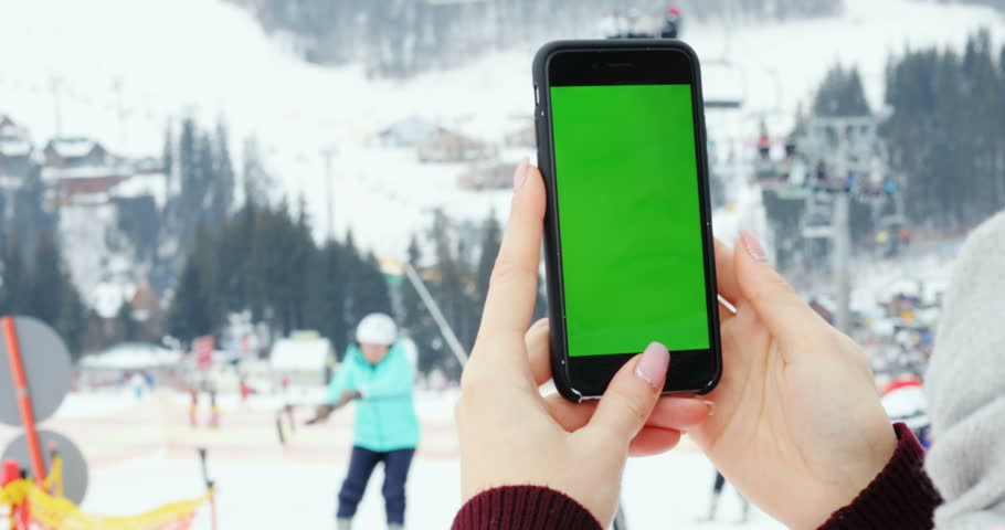 Close-up female hand using smart phone digital device green screen chroma-key mock up content mountains winter tapping ski lift people skiing technology internet connect 3G scrolling touchscreen | Shutterstock HD Video #1007567086