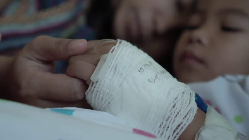 Young mother is holding hand bandaged of little daughter with love and care while they lying on bed in the hospital in slow motion shot