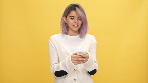 Happy woman in warm cardigan writing message on smartphone over yellow background