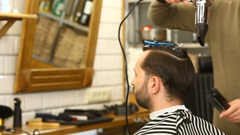 Barber blowdries and combs hair of client using hairdrier and brush. Barbershop. Profile of young man having his hairstyle done at barber's, hd