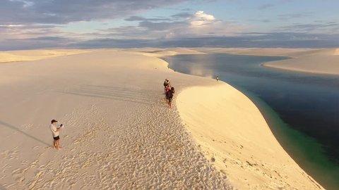 Barreirinhas, Maranhão / Brazil -  10/05/2017: Tourists on a dune at Lençóis Maranhenses National Park, during the sunset