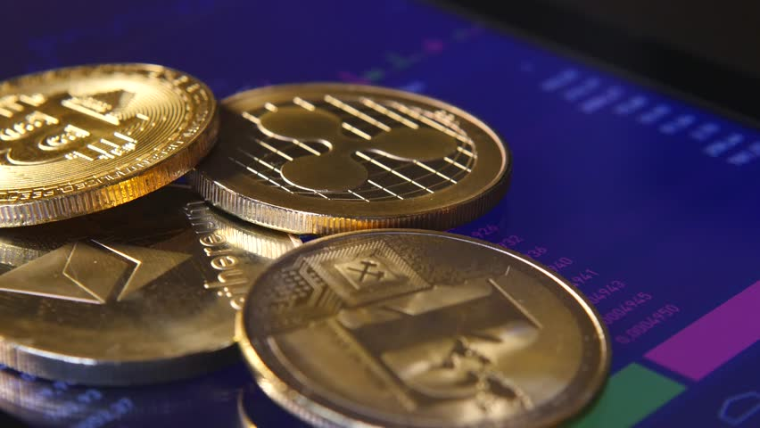 Golden cryptocurrency coins on the background of a graphic stock chart. | Shutterstock HD Video #1007594311