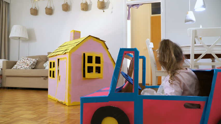 Funny little girl and her father are driving handmade cardboard car. Father and daughter are having fun in living room together.