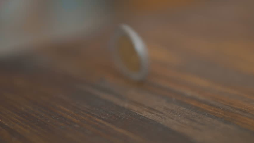 Coin Flip in Slow Motion with Alpha: A quarter flips through the air up from the bottom of the frame, reaches the apex of it's toss, and then falls out of frame. Alpha included. Shallow
