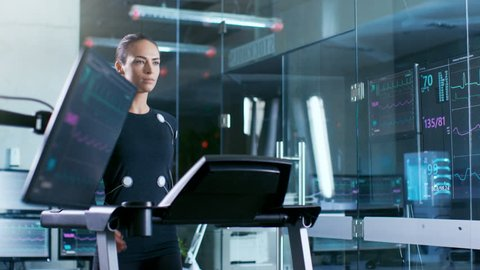 Beautiful Woman Athlete with Electrodes Connected to Her Body Walks on a Treadmill in a Sports Science Laboratory. In the Background High-Tech Laboratory with Monitors Showing EKG. RED EPIC-W 8K