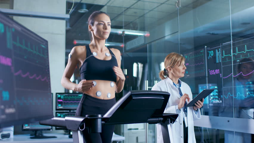 Woman Athlete Runs on a Treadmill with Electrodes Attached to Her Body, Female Physician Uses Tablet Computer and Controls EKG Data Showing on Laboratory Monitors. Shot on RED EPIC-W 8K Camera.