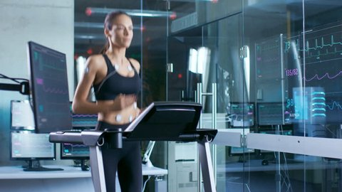 Beautiful Woman Athlete Runs on a Treadmill with Electrodes Attached to Her Body, Female Physician Uses Tablet Computer and Controls EKG Data Showing on Monitors. Shot on RED EPIC-W 8K  Camera.