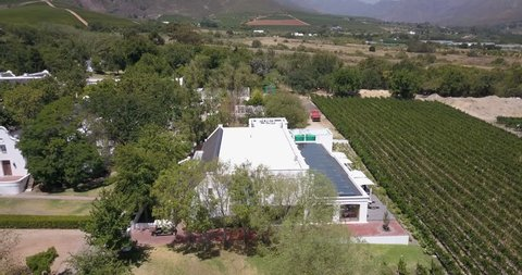4K summer day aerial video view of Western Cape's Stellenbosch wine estates area, Lanzerac's beautiful hilly garden and twin peaks view, grape plantations in background near Cape Town, South Africa
