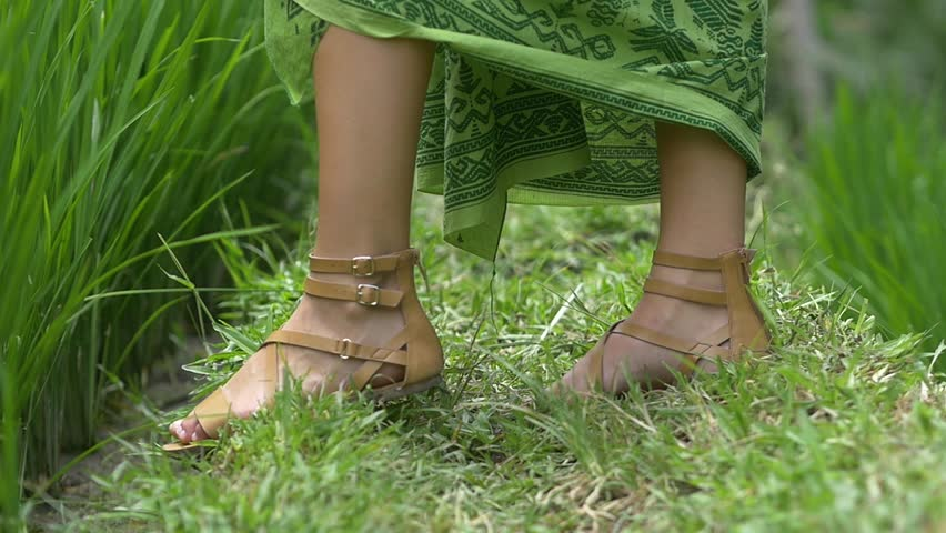 Caucasian female feet wearing sandals walking away on green Asian grass | Shutterstock HD Video #1007636914