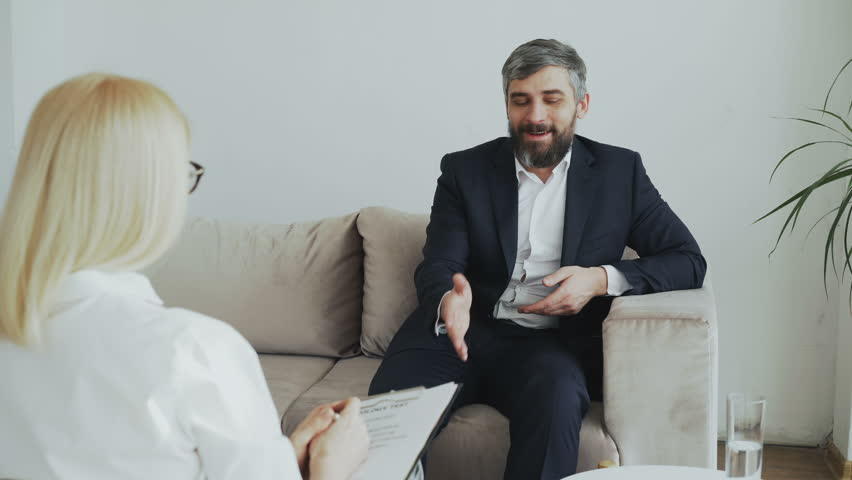 Smiling businessman sitting on couch talking to female psychologist in office