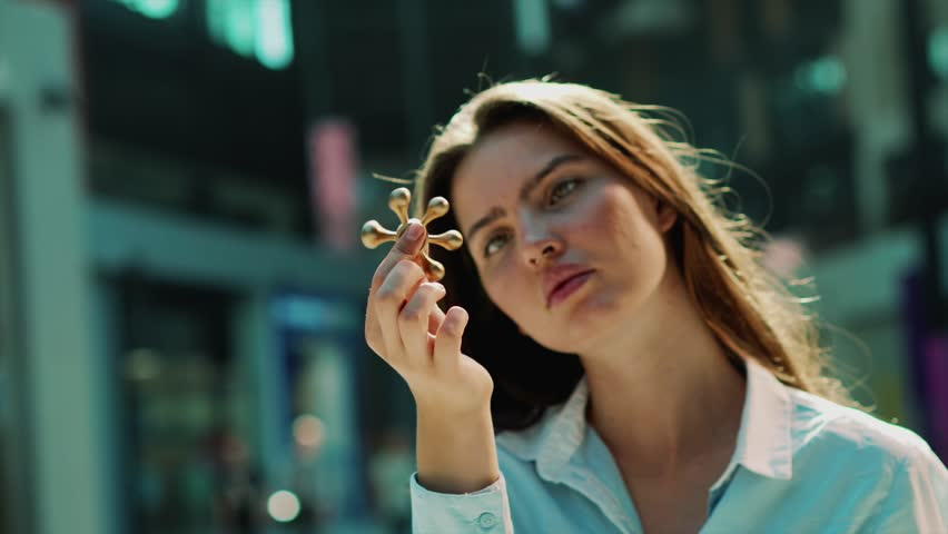 Beautiful brunette woman is keeping spinner in her hands in shopping mall. She is closely watching how golden spinner rolling. | Shutterstock HD Video #1007646814