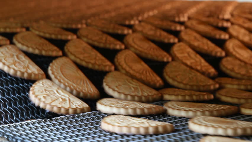 Cookies on a conveyor in a confectionery factory oven. Freshly baked shortbread cookies leave the oven. Production line of baking cookies. Conveyor with cookies. | Shutterstock HD Video #1007652478