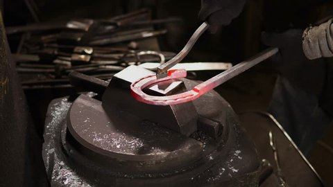 Worker is holding heated blank of horseshoe on a anvil of hydraulic hammer in a workshop of forge. Close-up of product, hands of man and instruments