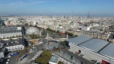 The city of Paris shot from the Paris Expo Porte de Versailles congress center / Paris drone footage on a clear blue sky / Eiffel Tower and Paris cityscape aerial footage.