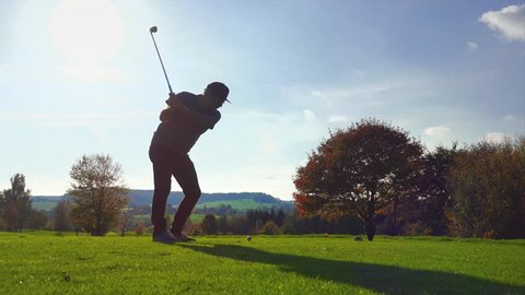 Golf Player plays golf on a beautiful summer morning. wide angle Lens flare Back lite shot