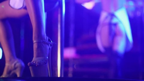 Stripper in shoes on high heels performs at stage of night club
