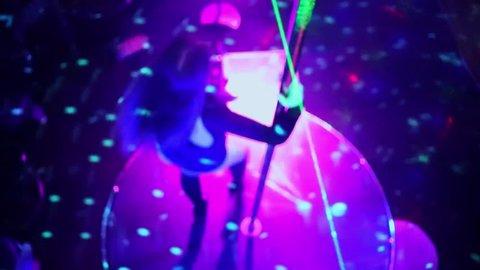 Stripper in black dress performs pole dance in night club, soft focus