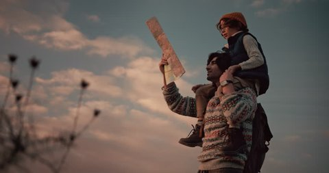 Young son on hiker father's shoulders reading map on trekking and camping adventure on mountains