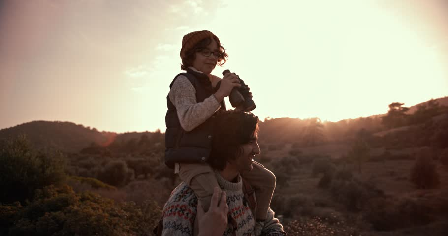 Young son on hiker father's shoulders using binoculars and looking at mountain view at sunset | Shutterstock HD Video #1007705188