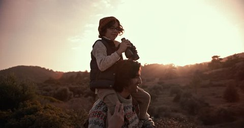 Young son on hiker father's shoulders using binoculars and looking at mountain view at sunset