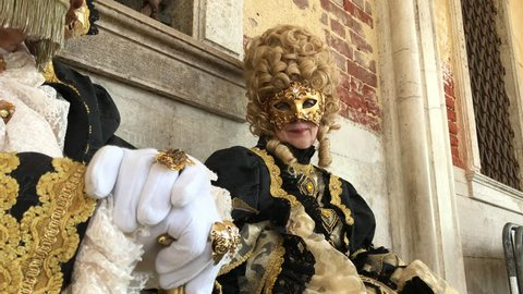 Venice, Italy - February 10 2018: Carnival mask and costume couple poses. Noble Masked couple in traditional golden costume pose at a Venetian square during the Venice 2018 Carnival.