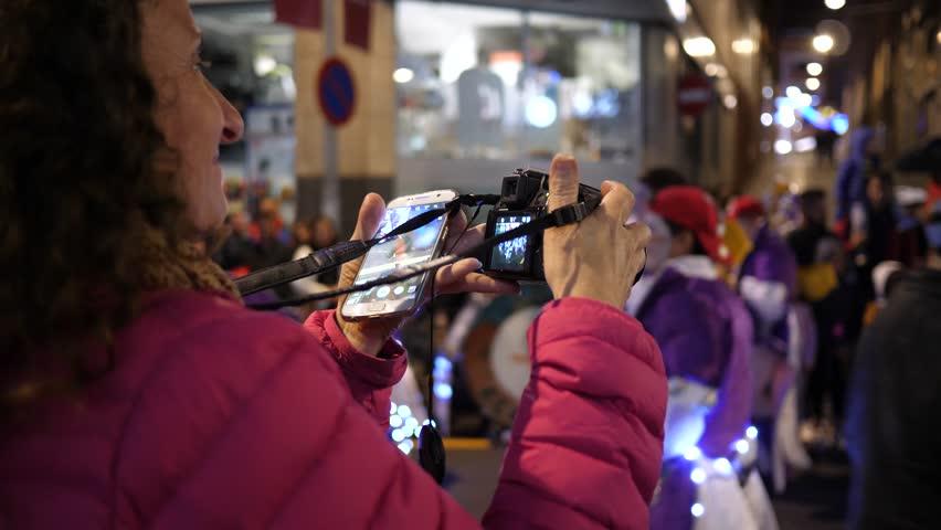 SANTA CRUZ DE TENERIFE - FEB 09, 2018: Spectator woman enjoy take mobile phone and camera pictures of the carnival procession   Shutterstock HD Video #1007723698