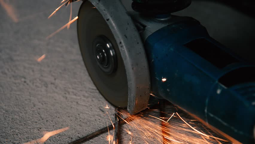 Sparks from grinding metal by a blue grinding machine loop on a gray beton background