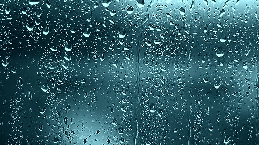 Close up of a window with rain drops falling down, Heavy rain on window. Rain splashing on a window, over a cloudy blue sky. ULTRA HD. 4K.