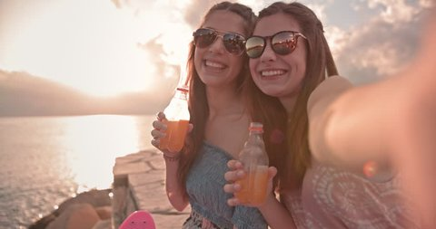 Teenage best friends taking selfies on smartphone, relaxing by the sea and drinking fizzy drinks