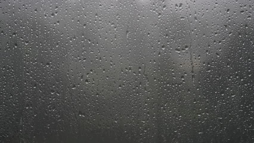 Cinematic 8K resolution 7680x4320 30p. There is a rain water drops in the window glass. There is a wooded park on the back plate background. Can be home or business office window. Sad in heavy rain.