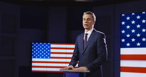 Public speaker or presenter in front of American flag standing at a small rostrum speaking and gesturing emphatically with his hands. 4K shot on Red cinema camera.