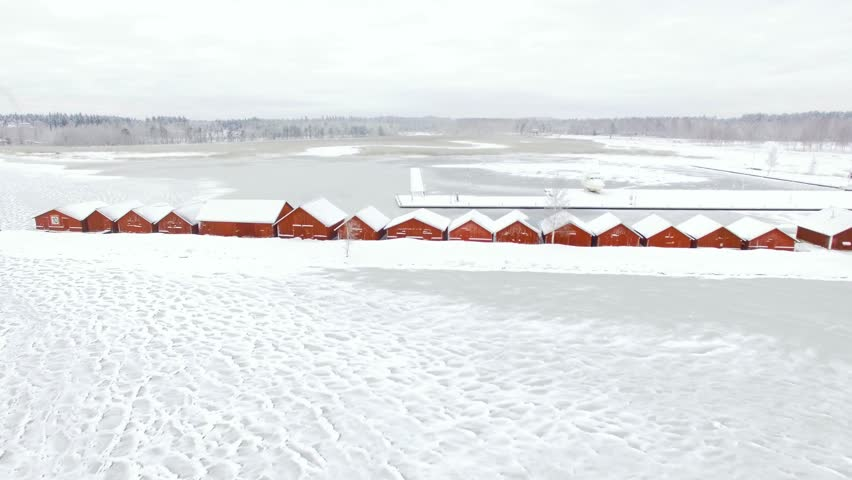 Flying over wooden red boathouses at a frozen lake in Finland.