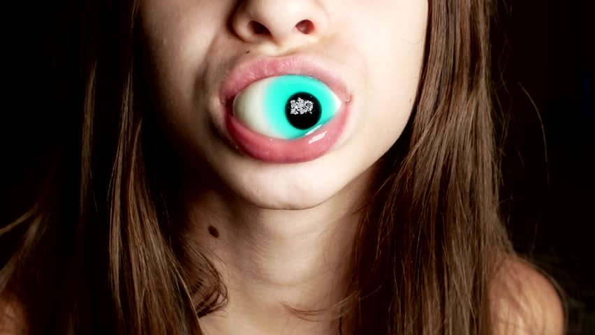 close-up. a cheerful teenage girl holds large round candies in her mouth, similar to the eyes. 4k.