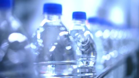 Clean water in plastic bottle moves through conveyor factory.