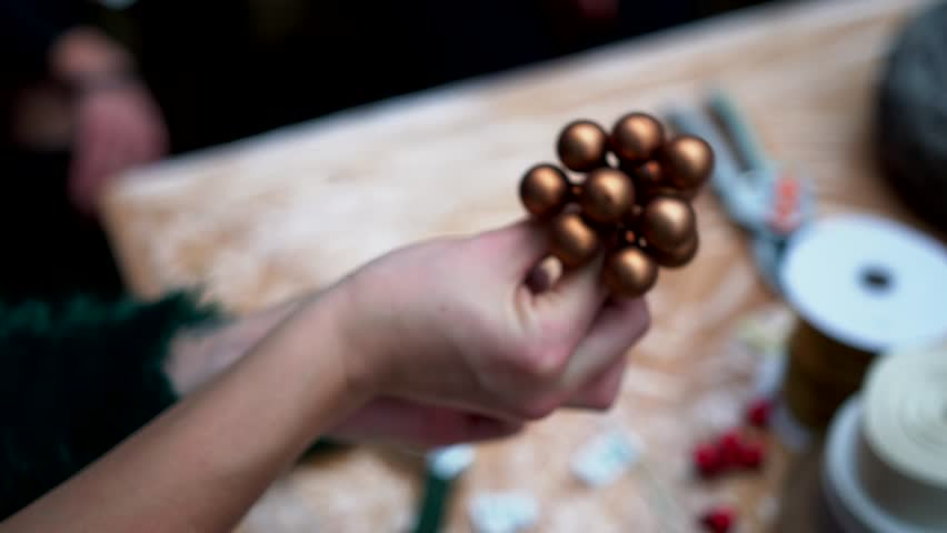 Female hands prepare faux berries for a handcrafted christmas table centerpiece arrangement: a basket with fir-tree branches, cotton balls and candles, close-up.