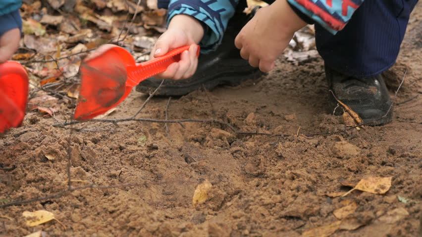 Hands of unknown child digging and playing with sand in sandbox and learning how to make shapes in an amusement park at autumn day. Close-up