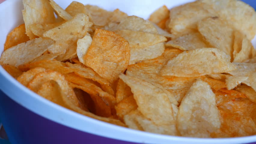 Beautiful well-groomed women's hands with a French manicure eat potato chips from a huge plate on the couch